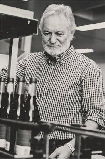 Man looking over some bottles of beer