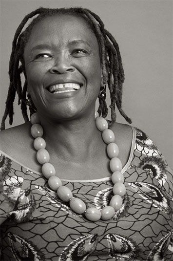 Greyscale image of a women wearing a large bead necklace smiling